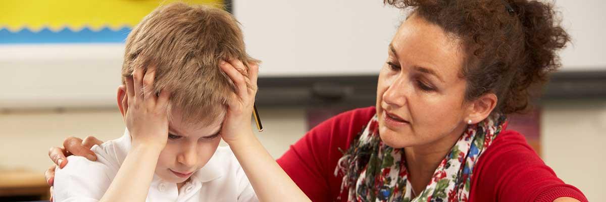 jongetje met handen in het haar wordt begeleid door lerares